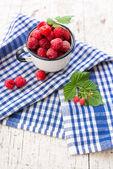Raspberries in an enamel cup — Stock Photo