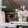 Carpenter working with Industrial tool in wood factory wearing safety glasses and hearing protection. — Stock Photo #78649556