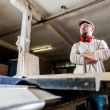 Carpenter working with Industrial tool in wood factory wearing safety glasses and hearing protection. — Stock Photo #78649560