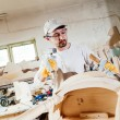 Carpenter working at a wood table with hammer and chisel. — Stockfoto #78649624
