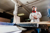Carpenter working with Industrial tool in wood factory wearing safety glasses and hearing protection. — Stock Photo