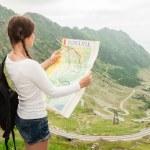 Girl tourist in mountain read the map. Transfagarasan road from Romania! — Stock Photo #78655998