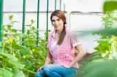 Vacker ung kvinna trädgårdsskötsel och ler mot kameran. — Stockfoto