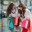 Two beautiful women looking inside shopping bags in the city over shop windows background — Stock Photo #79946088