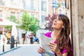 Young woman tourist holding a paper map in Plaza Mayor square, Madrid, Spain, looking for direction. — Stock Photo