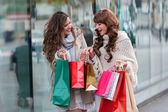 Two attractive young women shopping together, — Stock Photo