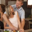 Loving couple smiles at each other while making dinner together — Stock Photo #53545625