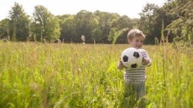 Little boy walking through grass with soccer ball — Vídeo Stock