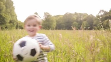 Little boy playing with soccer ball in park — Stock Video
