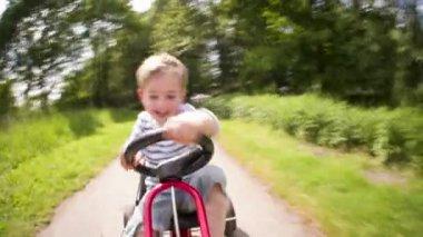 Little boy having fun driving a pedal car — Stock Video