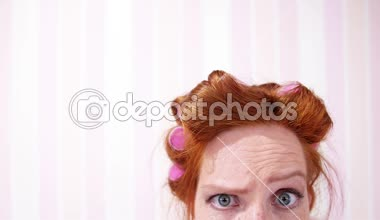 Red-haired girl in hair curlers — Stock Video
