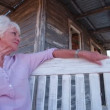 Senior woman relaxing on front porch — Stock Video #69850867