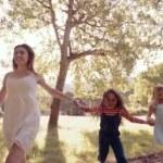 Woman running with kids through park — Vídeo de stock #69856633