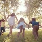 Woman running with kids through park — Vídeo de stock #69856715