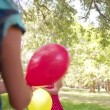 Girls having fun with bright balloons — Stock Video #69856725