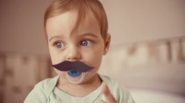 Baby boy touching a paper mustache — Stock Video