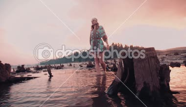 Boho girl walking through a shallow lake — Stock Video