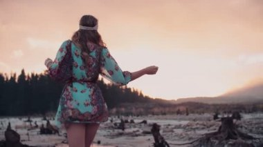 Boho Girl standing in water at sunset — Stock Video