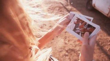 Menina olhando fotos instantâneas ao ar livre — Vídeo stock