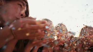 Teens blowing colorful confetti outdoors — Stock Video