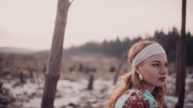 Boho girl in a headband sitting in nature — Stock Video