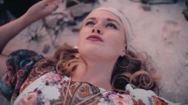 Boho girl lying down on sand — Stock Video