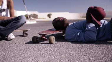 Longboarders sitting and lying on longboards — Stock Video