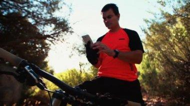 Mountain biker looking at smartphone — Стоковое видео