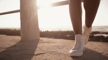 Girl wearing sneaker standing at seaside — Stock Video
