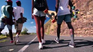 Teenage longboarders walking on a road — Stockvideo