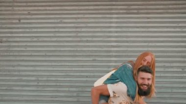 Girl laughing while hipster boyfriend piggyback — 图库视频影像