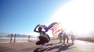 Buz pateni yaparken bir Amerikan bayrağı uçan kaykaycılar — Stok video