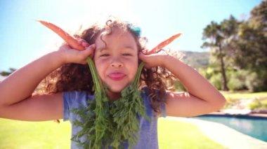 Little girl posing with carrots as ears — Vídeo de Stock