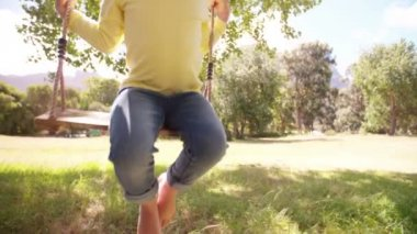 Girl swinging under trees — Stock Video