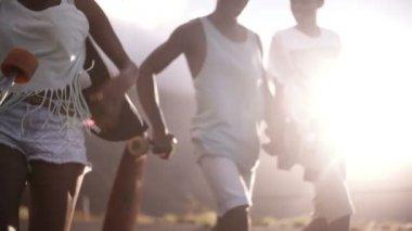 American teenage longboarders walking on road — Stock Video