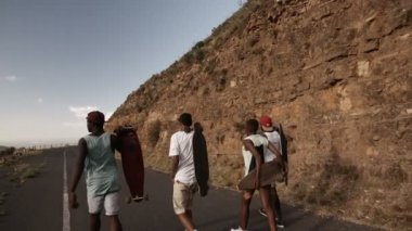 Teen skateboarders walking along road — Stock Video