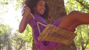 Afro girl swinging playfully in park — Stock Video