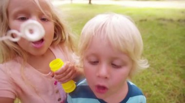 Girl and boy blowing bubbles — Stock Video