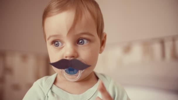 Niño tocando un bigote de papel — Vídeo de stock