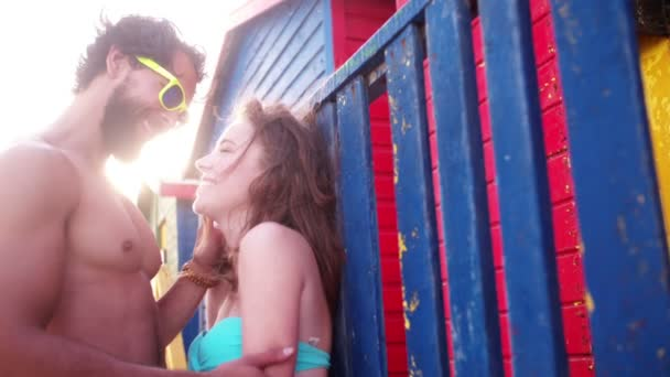 Couple kissing in front of beach huts — Vidéo