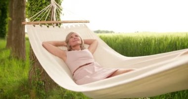 Mature woman relaxing and daydreaming outdoors — Stock Video