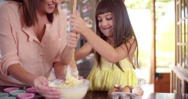 Flickan att hjälpa sin mamma genom omrörning ingredienserna till kakan — Stockvideo