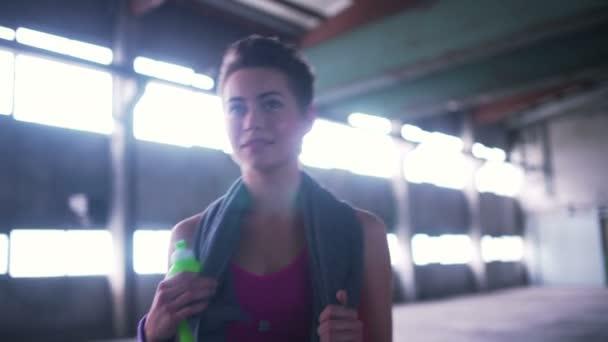 Chica en ropa deportiva con una toalla — Vídeo de stock