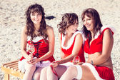 Happy friends in santa hats on the beach. Christmas vacation — Foto Stock