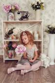 Cute little child girl with spring flowers, happy baby girl with basket of flowers. — Stock Photo