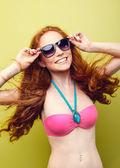 Beautiful bikini woman smiling on green background. — Stock Photo