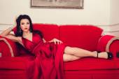 Sexy glamour woman with black hair in elegant red dress in luxury bedroom — Stock Photo