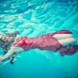 Young sexy woman floating on swimming pool in red dress. beauty shot — Stock Photo #76891303
