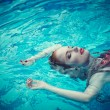 Young sexy woman floating on swimming pool in red dress. beauty shot — Stock Photo #76891327