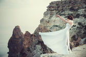 Beautiful bride posing on the coast with angelic dress — Stock Photo